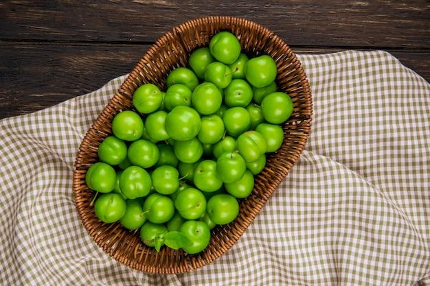 Widok z góry zielonych kwaśnych śliwek w wiklinowym koszu na szkockiej kracie na ciemnym drewnianym stole