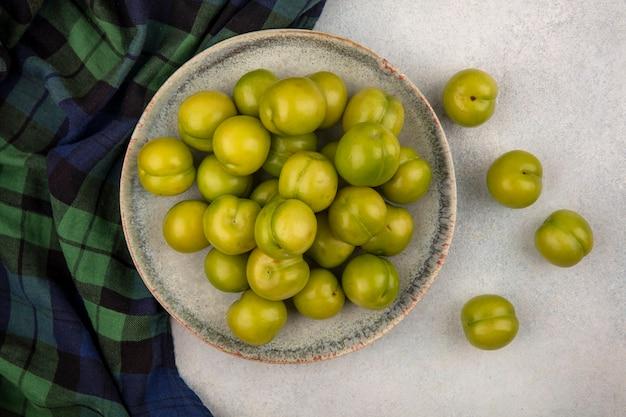 Widok z góry zielonych śliwek na talerzu na kratę i na białym tle