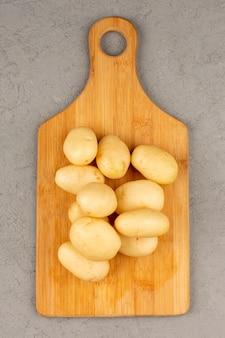 Widok z góry ziemniaki obrane w całości na szarym tle