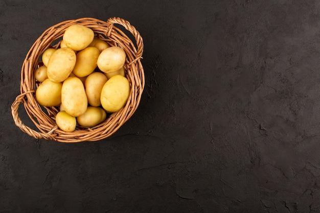 Widok z góry ziemniaki w koszu na ciemnej podłodze