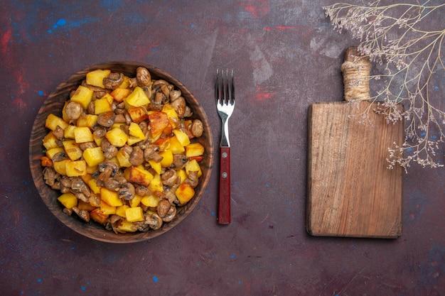 Widok z góry ziemniaki z grzybami miska z ziemniakami i widelcem do pieczarek i drewniana deska do krojenia warzyw