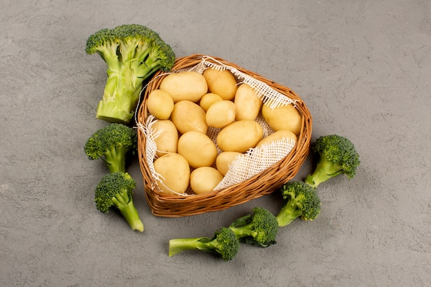 Widok z góry ziemniaki z zielonymi brokułami świeżymi dojrzałymi na szarym tle