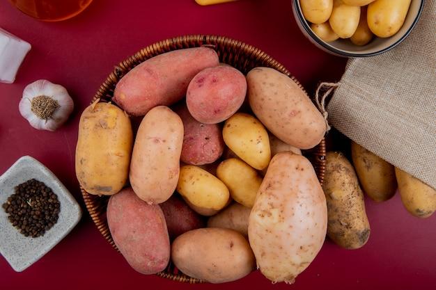 Widok z góry ziemniaków w koszu z czosnkiem nasiona pieprzu czarnego sól na powierzchni bordo