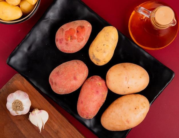 Widok z góry ziemniaków w talerzu z innymi w misce stopił masło i czosnek na desce do krojenia na tle bordo