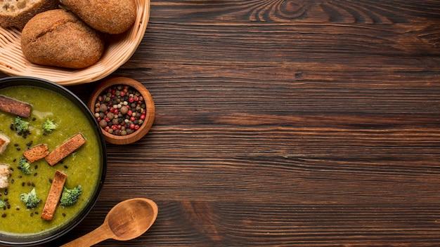 Widok z góry zimowej zupy brokułowej z miejsca na kopię i chlebem