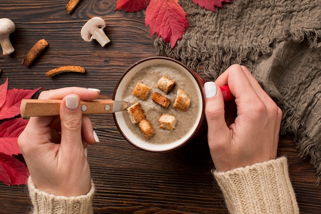 Widok z góry zimowej zupy grzybowej w kubku z łyżką trzymając się za ręce