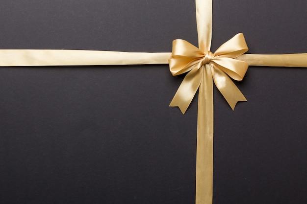 Widok z góry złotą wstążkę walcowane i yellowbow na białym tle na kolorowym tle. płaski układ z miejscem na kopię