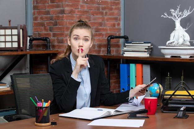 Widok z góry zmartwionej kobiety siedzącej przy stole i trzymającej dokument wykonujący gest ciszy w biurze