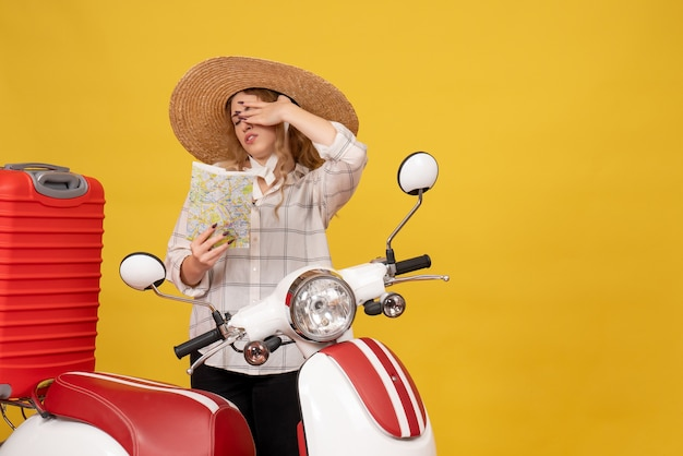 Widok z góry zmęczona młoda kobieta w kapeluszu, zbierając swój bagaż, siedząc na motocyklu i trzymając mapę
