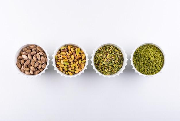 Widok z góry zmielone, zmielone, kruszone lub granulowane pistacje w miskach na białym tle