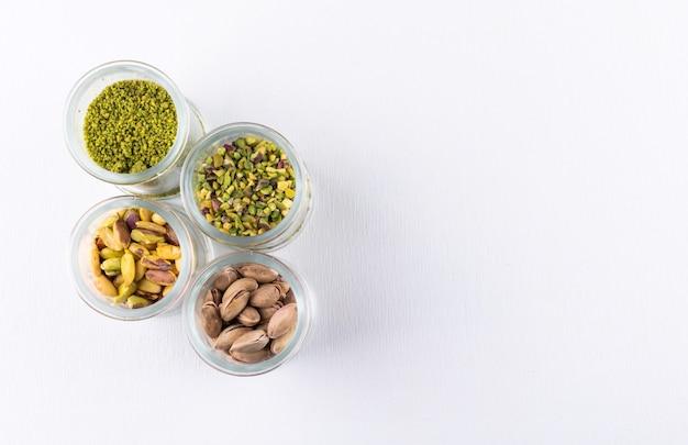 Widok z góry zmielone, zmielone, kruszone lub granulowane pistacje w szklanych słoikach na białym tle