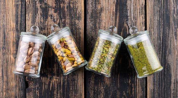 Widok z góry zmielone, zmielone, kruszone lub granulowane pistacje w szklanych słoikach na ciemnym drewnie