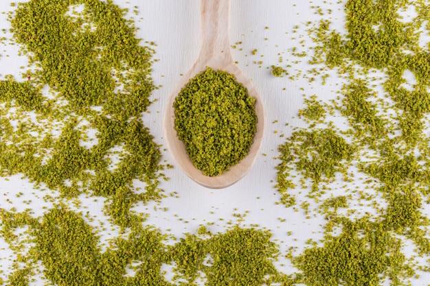 Widok z góry zmielone, zmielone, zmiażdżone pistacje w drewnianych łyżkach na białym tle