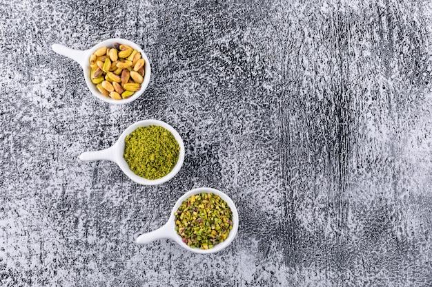Widok z góry zmielone, zmielone, zmiażdżone pistacje w misce na szarej fakturze