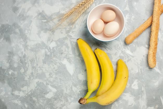 Widok z góry żółte banany z surowymi jajkami i bułką na jasnym białym biurku