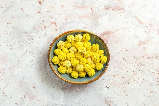 Widok z góry żółte cukierki wewnątrz talerza na białym słodkim cukrze cukrowym