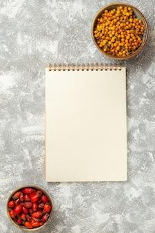 Widok z góry żółte jagody z notatnikiem na białym tle