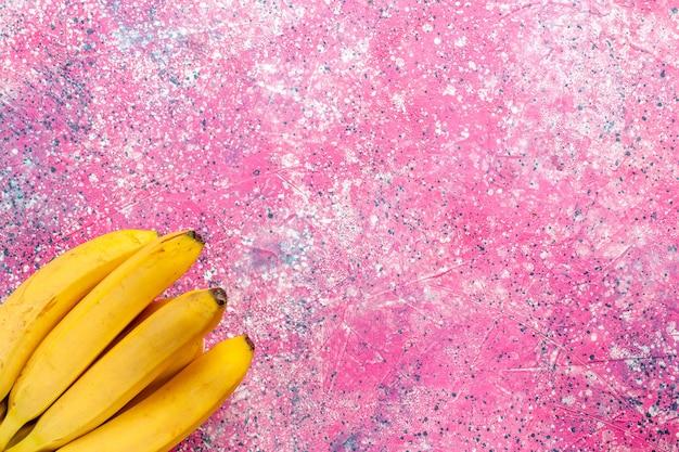 Widok z góry żółte świeże banany pyszne owoce na różowej powierzchni