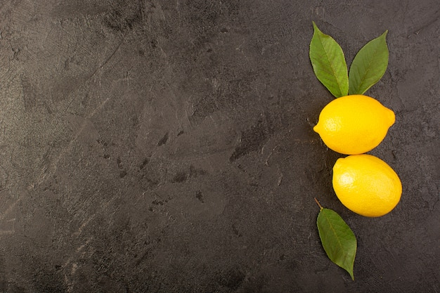Widok z góry żółte świeże cytryny łagodne i soczyste w całości i pokrojone w zielone liście na ciemnym tle owoce cytrusowe