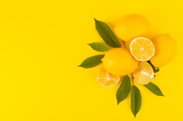 Widok z góry żółte świeże cytryny świeże dojrzałe w całości i pokrojone wraz z zielonymi liśćmi owoce odizolowane na żółtym tle kolor owoców cytrusowych