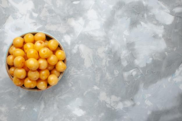 Widok z góry żółte wiśnie słodko świeże, łagodne owoce wewnątrz talerza na lekkim biurku owoce świeże słodkie zdjęcie kolor