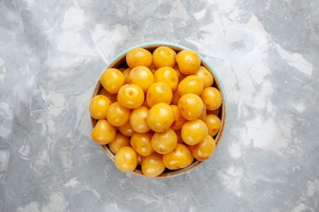 Widok z góry żółte wiśnie wewnątrz brązowego talerza na jasnoszarym zdjęciu owocowym na biurku