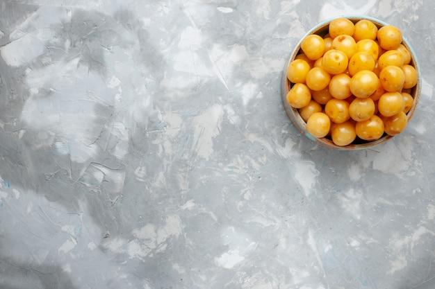 Widok z góry żółte wiśnie wewnątrz okrągłego talerza na szarym tle owoce świeże słodkie zdjęcie kolor