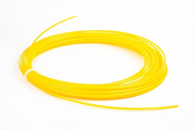 Widok z góry żółtego walcowanego tworzywa sztucznego do druku 3d na białym tle.