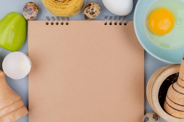 Widok z góry żółtka jaja i bieli na niebieskiej misce z zieloną papryką na białym tle z miejsca kopiowania
