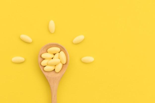 Widok z góry żółty lek w drewnianej łyżce