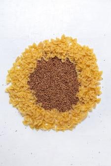 Widok z góry żółty surowy makaron trochę uformowany z kaszą gryczaną na białym biurku makaron włochy jedzenie posiłek