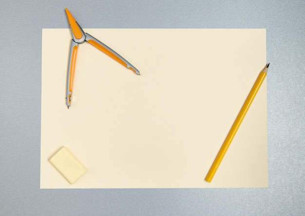 Widok z góry żółtych narzędzi do rysowania. ołówek, kompas, gumka i kartka papieru na szarej powierzchni