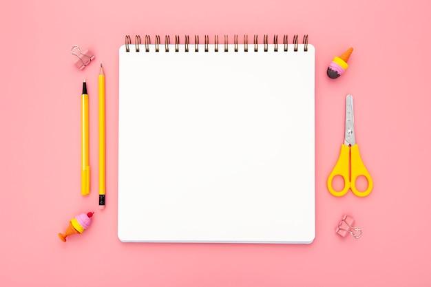 Widok z góry zorganizowany układ elementów biurka na różowym tle