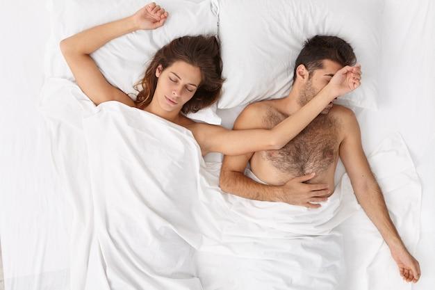 Widok z góry zrelaksowanej kobiety rozciąga ręce podczas snu z mężem, pozuje na białym łóżku w przytulnej sypialni, mężczyzna odczuwa dyskomfort. para odpoczywa razem, ma głęboki sen. czas spać, koncepcja odpoczynku.