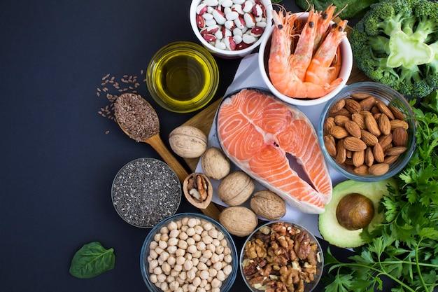 Widok z góry źródeł żywności omega 3 na czarnym tle. skopiuj miejsce. pokarm bogaty w kwasy tłuszczowe.