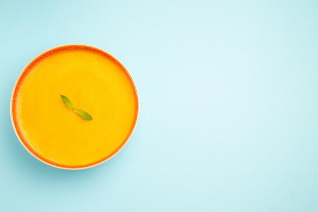 Widok z góry zupa dyniowa wewnątrz płyty na niebieskim biurku