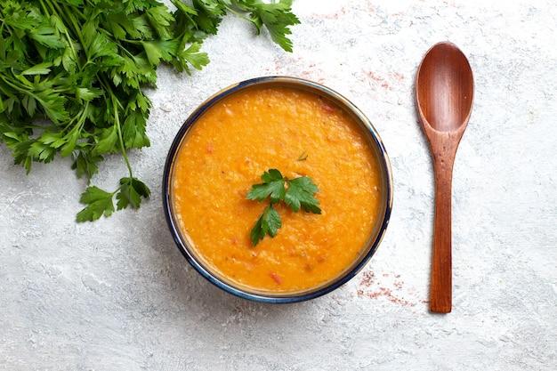 Widok z góry zupa fasolowa zwana merci wewnątrz małego talerza z zieleniną na białej powierzchni zupa posiłek jedzenie fasola warzywna