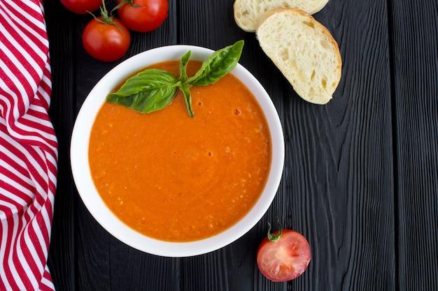 Widok z góry zupa pomidorowa w białej misce na czarnej powierzchni drewnianych