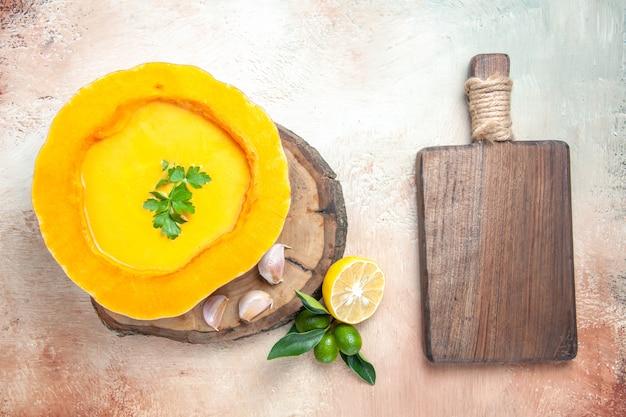Widok z góry zupa z dyni z ziołami, czosnkiem, cytryną deska do krojenia