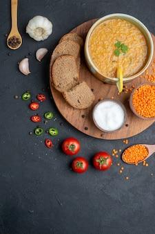 Widok z góry zupa z soczewicy z soloną surową soczewicą i ciemnymi bochenkami chleba na ciemnej powierzchni