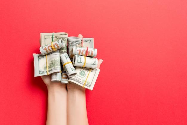 Widok z góry zwinięte w rurki dolary w żeńskich dłoniach