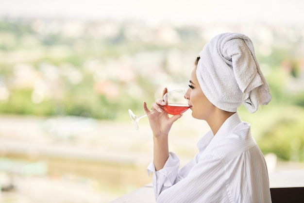 Widok z hotelowego okna na dziewczynę relaksującą się w szlafroku z białym kieliszkiem wina pali papierosa