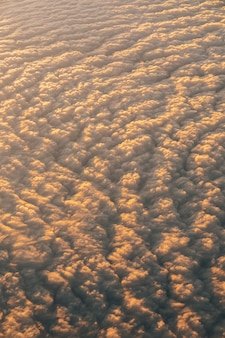 Widok z iluminatora na chmury na niebie o zachodzie słońca