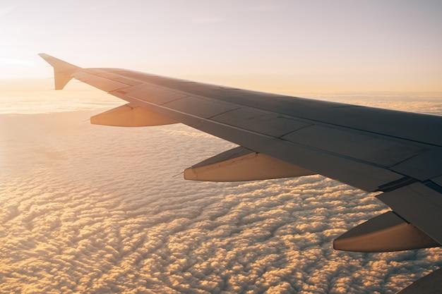 Widok z iluminatora na skrzydle samolotu i chmur pod nim o zachodzie słońca