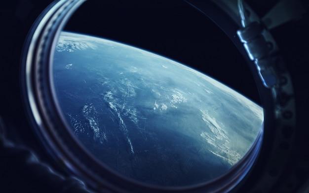 Widok z iluminatora statku kosmicznego. ziemia i statek kosmiczny.