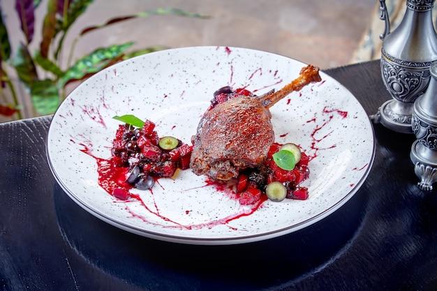 Widok z kaczki na udko udekorowane jagodowymi plamami i jagodami na białym talerzu. skopiuj miejsce tło jedzenie mięsa. ścieśniać. confit z kaczki. resturacyjne jedzenie