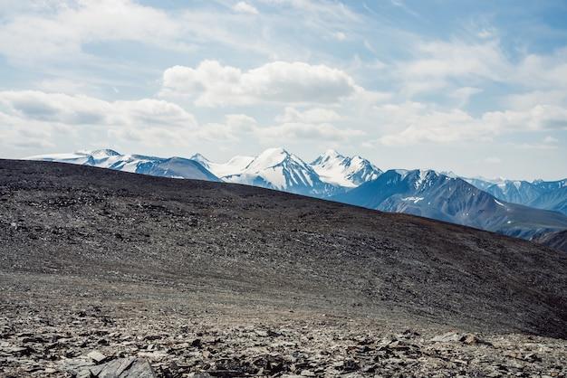 Widok z kamienistej przełęczy na zaśnieżone pasmo górskie.
