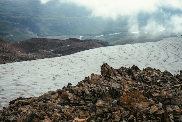 Widok z krawędzi przepaści z ostrymi skałami i gzymsem śnieżnym na górską dolinę w niskich chmurach. wspaniała górska sceneria z niskimi chmurami w górskiej dolinie. malowniczy alpejski krajobraz ze skalistymi górami