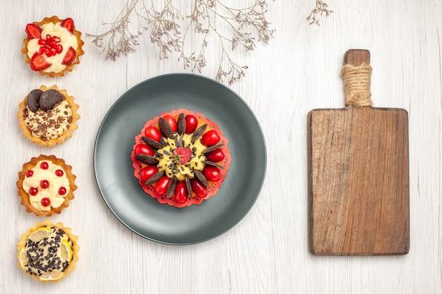 Widok z lewej strony u góry ciasto jagodowe na szarym talerzu i od góry do dołu różne tarty i deska do krojenia na białym drewnianym podłożu