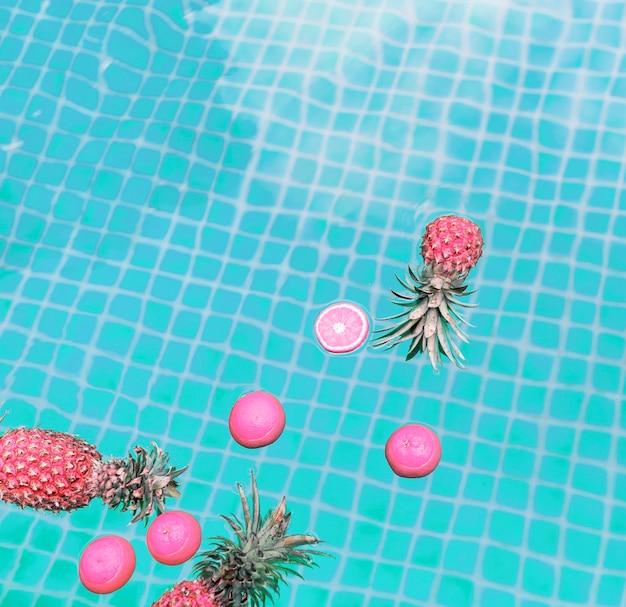 Widok z lotu ptaka ananas i pomarańcze unosi się w pływackim basenie